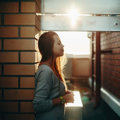 52665575 - young woman standing on a street with closed eyes in sunset light. selective focus, lens flare.